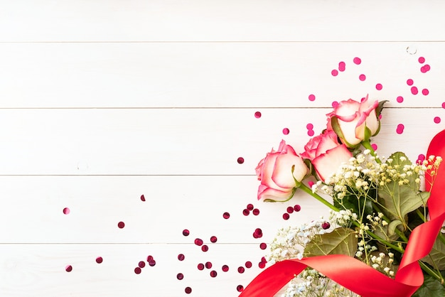 Conceito de dia dos namorados. rosas cor de rosa com confete em fundo branco de madeira