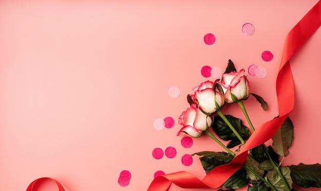 Conceito de dia dos namorados. rosas cor de rosa com confete em fundo rosa sólido