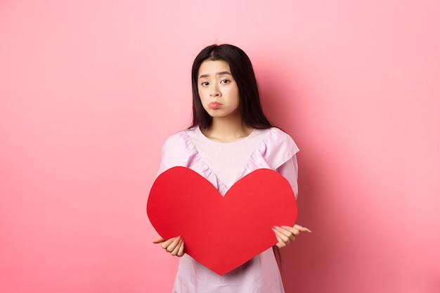 Conceito de dia dos namorados. solteira adolescente asiática quer se apaixonar, parecendo triste e solitária para a câmera, amuado e angustiado no dia dos namorados, segurando um recorte de coração vermelho grande, fundo rosa.