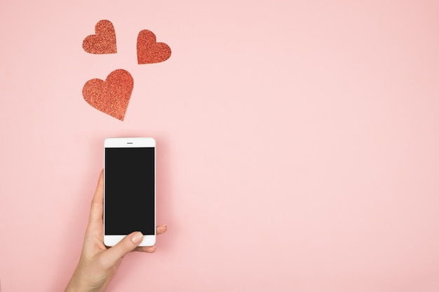 Conceito de dia dos namorados, tela do telefone móvel na mão com corações vermelhos na superfície rosa. amor nas redes sociais