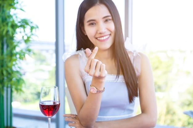 Conceito de dia dos namorados, uma forma de coração ou mini coração feito à mão de uma jovem asiática feliz sentada à mesa com uma comida com taças de vinho e buquê de rosas vermelhas e cor de rosa no fundo do restaurante