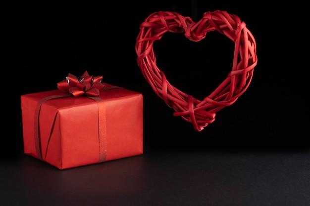 Conceito de dia dos namorados. vime levitando coração vermelho e caixas de presente em fundo preto. greeeting cartão, cartão postal