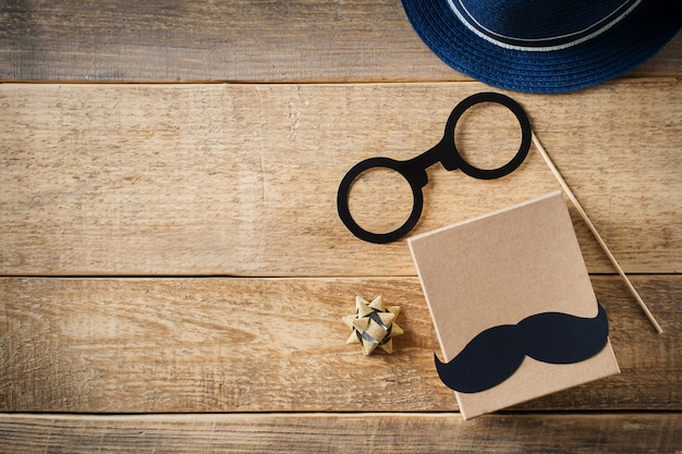 Conceito de dia dos pais com bigode e acessórios masculinos sobre fundo de madeira