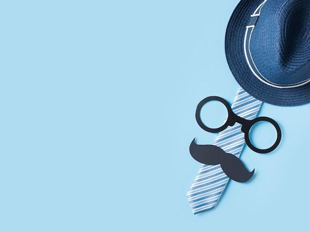 Conceito de dia dos pais com chapéu, óculos e gravata em fundo azul