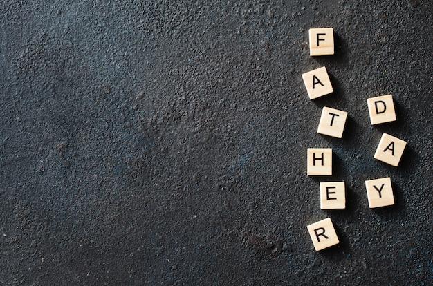 Conceito de dia dos pais. letras de madeira em fundo escuro.