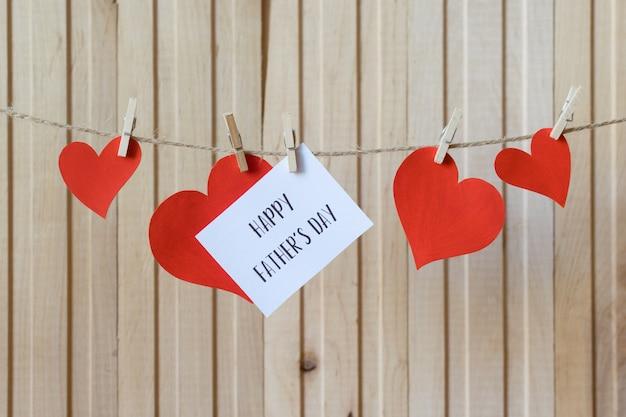 Conceito de dia dos pais. mensagem com os corações de papel que penduram com os pregadores de roupa sobre a placa de madeira leve.