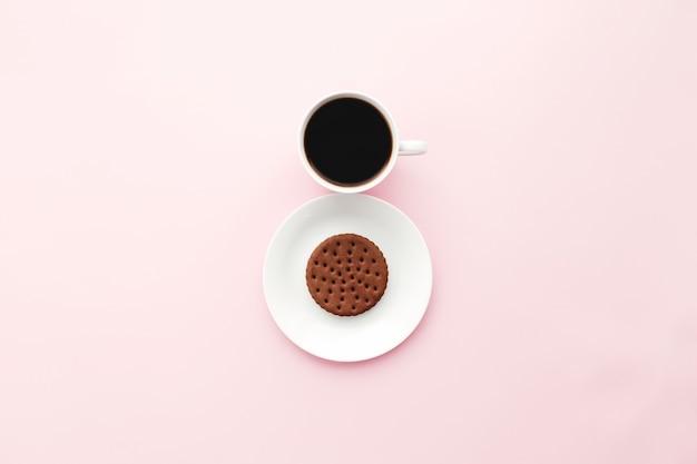 Conceito de dia internacional de mulher, xícara de café, prato, biscoito em fundo rosa. foto de alta qualidade