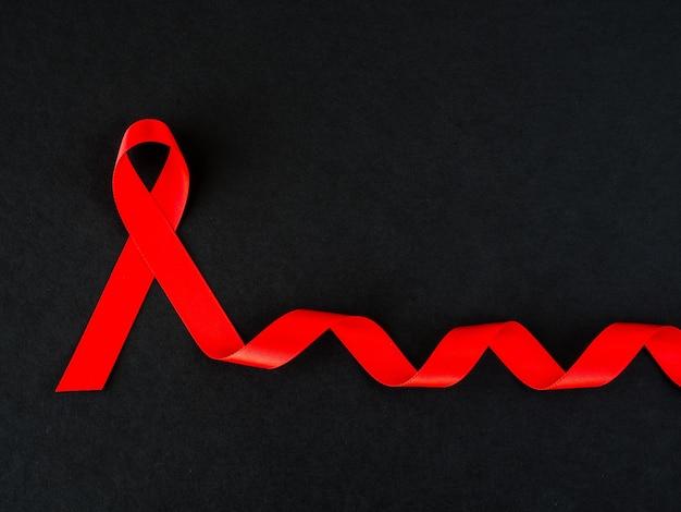 Conceito de dia mundial da aids. fita vermelha no fundo preto.