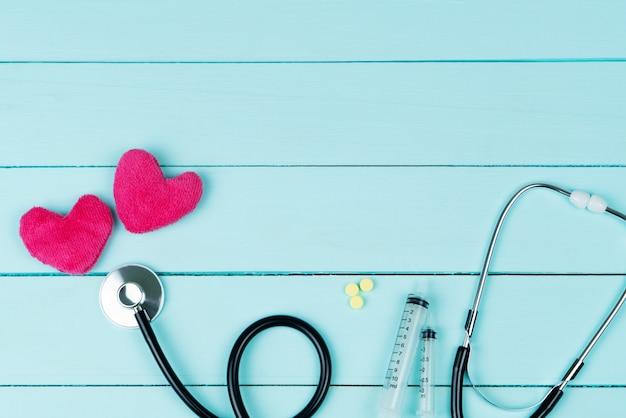 Conceito de dia mundial da saúde do coração e seguro médico de saúde com coração vermelho e estetoscópio no azul