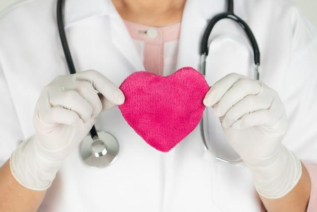 Conceito de dia mundial da saúde do coração e seguro médico de saúde com médico com estetoscópio segurando coração vermelho