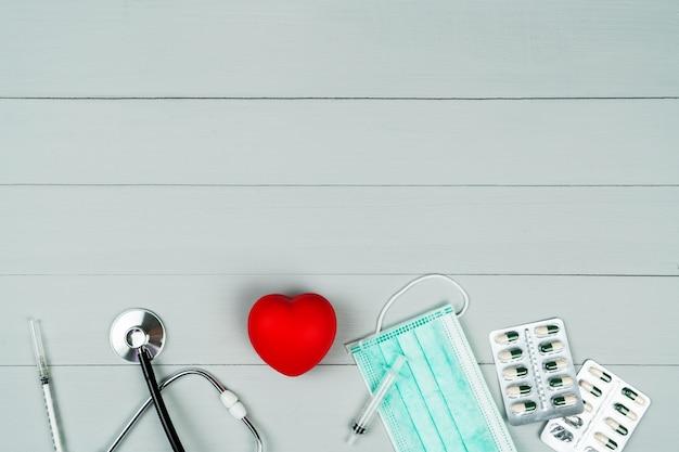 Conceito de dia mundial da saúde e seguro médico de saúde com coração vermelho e instrumento médico em fundo de madeira