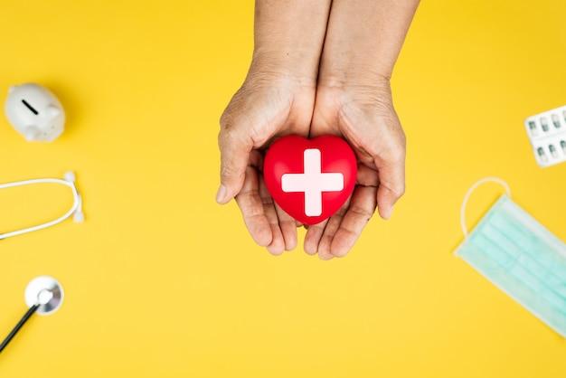 Conceito de dia mundial da saúde seguro médico de saúde com coração vermelho nas mãos da mulher sênior