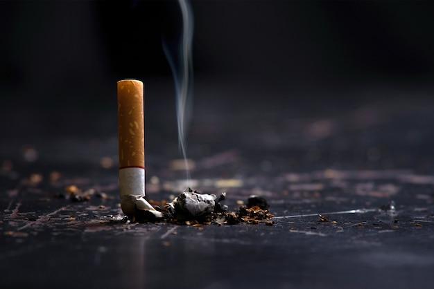 Conceito de dia sem tabaco mundo parar de fumar. bunda de cigarro de tabaco no chão