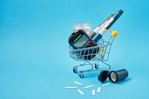 Conceito de diabetes. suprimentos para diabéticos no carrinho da loja em um fundo azul.
