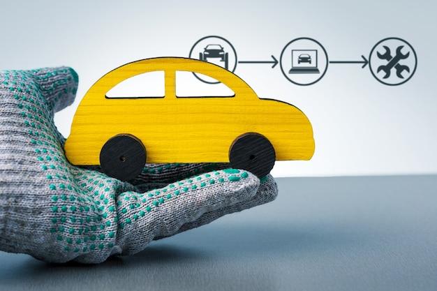 Conceito de diagnóstico e reparo do carro. técnico examinando carro de brinquedo e infográfico em fundo cinza.