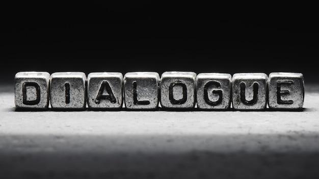 Conceito de diálogo. a inscrição em cubos 3d de metal isolados em um fundo preto