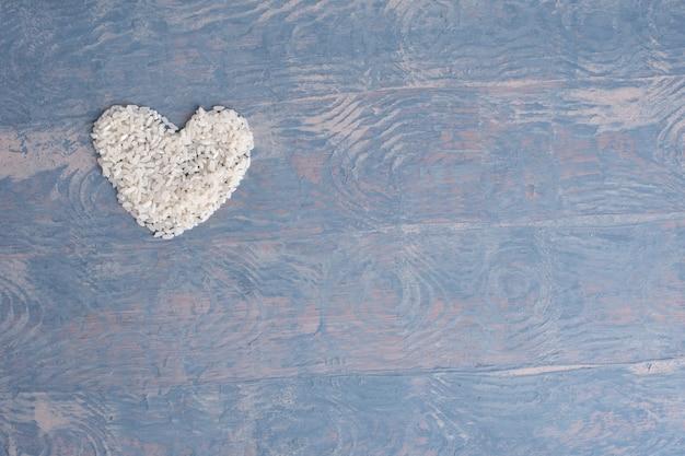 Conceito de dieta alimentar. arroz cru em forma de coração sobre fundo azul de madeira, cópia espaço, vista superior.