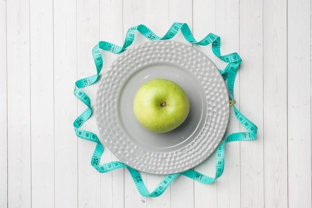 Conceito de dieta. apple verde em um centímetro da placa e da fita em uma tabela branca.