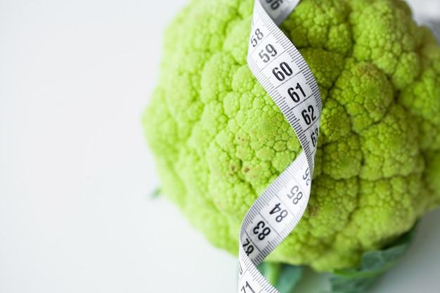 Conceito de dieta. brócolis com a fita métrica