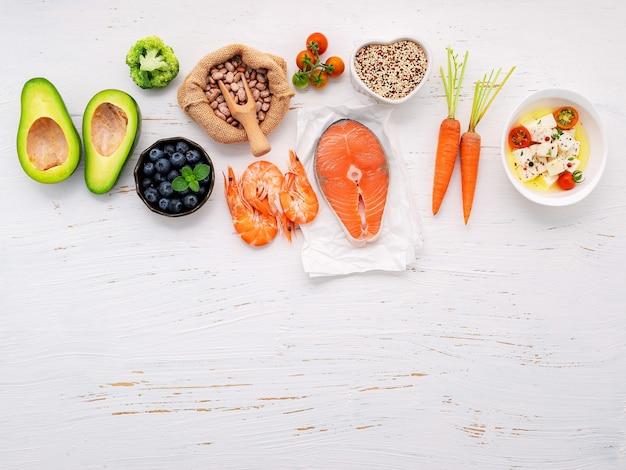 Conceito de dieta cetogênica de baixo teor de carboidratos. ingredientes para seleção de alimentos saudáveis configurados em fundo branco de madeira.