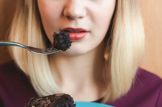 Conceito de dieta. closeup de garota comendo bolo de chocolate