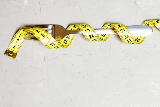 Conceito de dieta com garfo embrulhado em fita métrica em fundo cinza. vista superior da perda de peso com espaço vazio.