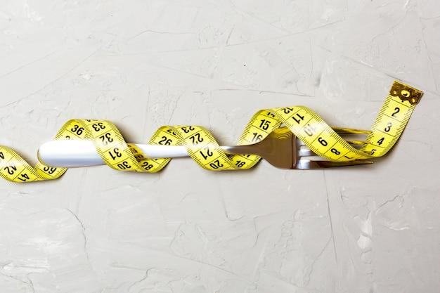 Conceito de dieta com garfo envolto em fita métrica