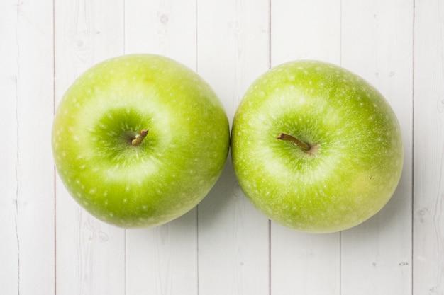 Conceito de dieta. duas maçãs verdes em uma tabela branca.