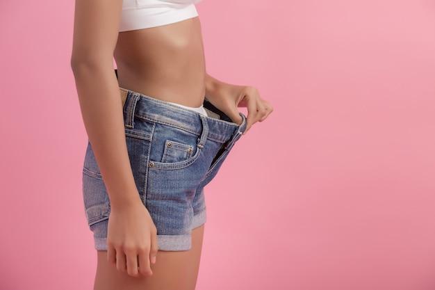 Conceito de dieta e perda de peso. mulher, em, oversize, calças brim