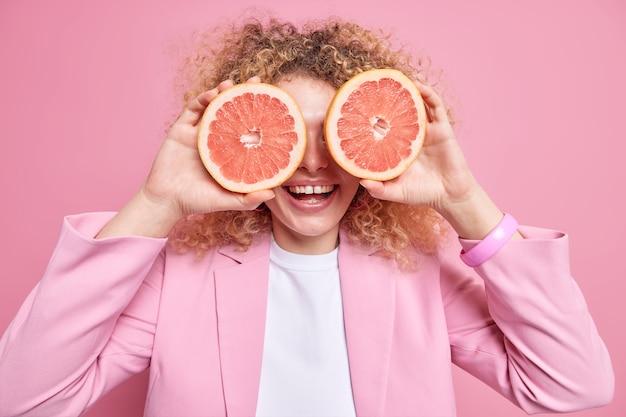 Conceito de dieta e vitaminas de bem-estar. mulher de cabelo encaracolado positiva cobre os olhos com metades de toranja usa frutas cítricas para refrescar a pele e sorri amplamente usa jaqueta formal isolada na parede rosa