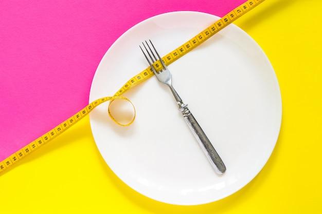 Conceito de dieta. garfo em um prato branco com centímetro.