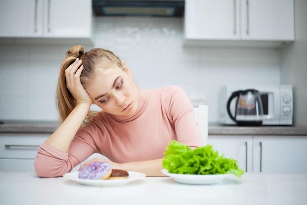 Conceito de dieta. jovem mulher escolhendo entre frutas e doces
