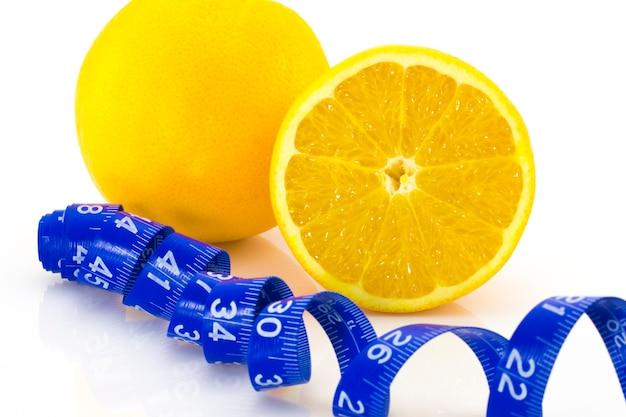 Conceito de dieta laranja madura e fita métrica isolada no fundo branco