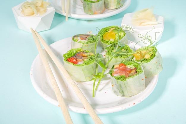 Conceito de dieta mediterrânea, nórdica e ceto. sushi sem arroz, comida diet com frutos do mar, vegetais. rolinhos primavera asiáticos modernos com estilo de sushi sobre fundo azul moderno