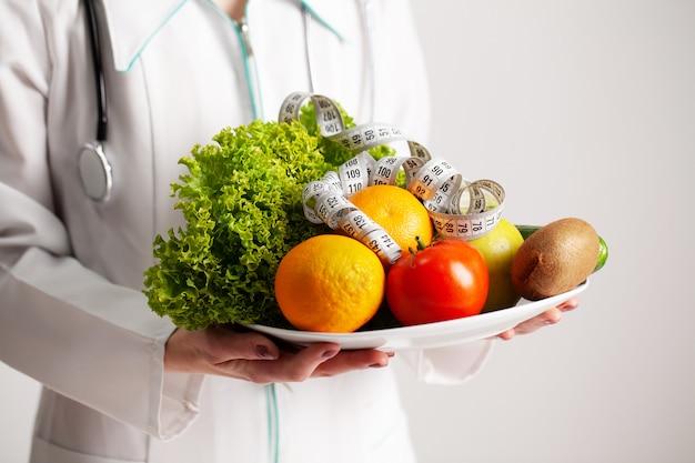 Conceito de dieta, nutricionista, segurando um prato cheio de frutas frescas com fita métrica