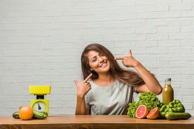 Conceito de dieta. o retrato de uma mulher latin nova saudável sorri, apontando a boca, conceito dos dentes perfeitos, dentes brancos, tem uma atitude alegre e jovial