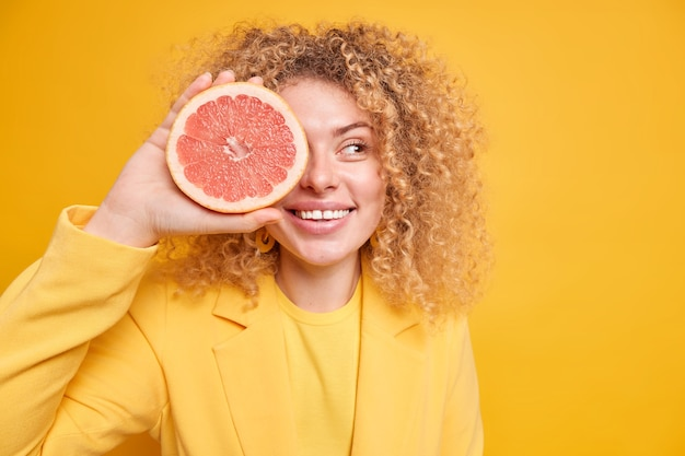 Conceito de dieta orgânica. mulher de cabelo encaracolado satisfeita cobre os olhos com meio sorriso toranja indo fazer suco fresco ou smoothie olha poses de lado contra a parede amarela copie a área do espaço para o texto