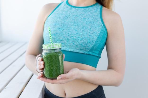 Conceito de dieta saudável, desintoxicação e perda de peso - jovem mulher em roupas esportivas com suco verde perto