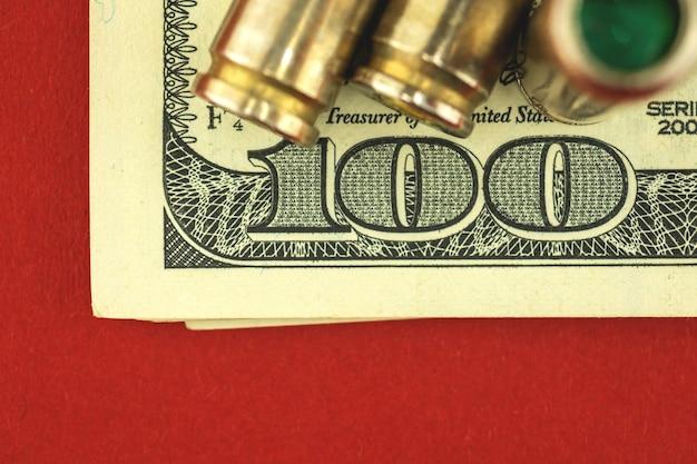 Conceito de dinheiro criminoso e sangrento com notas de cem dólares e munições, bala para arma, foto de close-up
