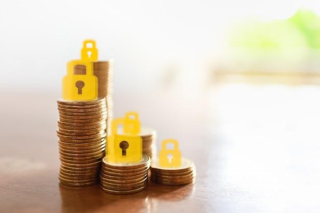 Conceito de dinheiro, finanças, aposentadoria e segurança. feche acima da pilha de moedas de ouro com o ícone de cadeado da chave mestra em cima de cada pilha com espaço de cópia.