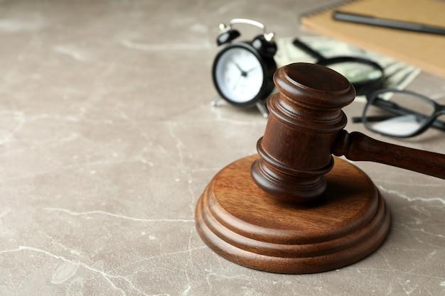 Conceito de direito com martelo de juiz na mesa texturizada cinza