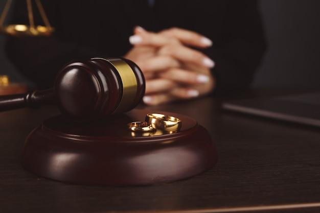 Conceito de direito da família, martelo do juiz e anéis de casamento em fundo de madeira.