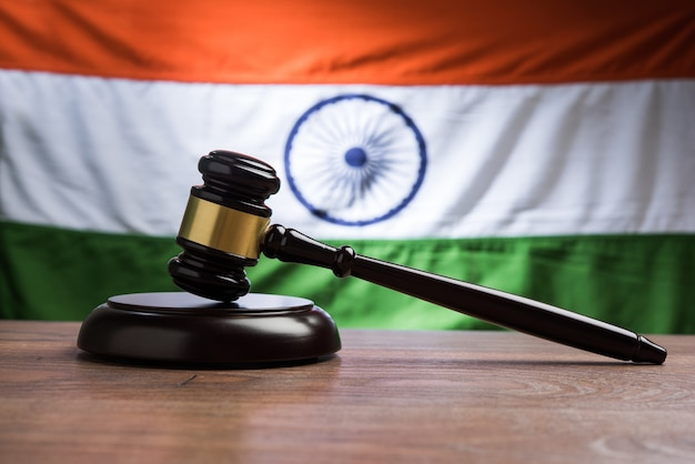 Conceito de direito indiano mostrando martelo de madeira e bandeira indiana