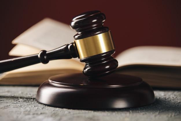 Conceito de direito - livro de direito aberto com um martelo de madeira do juiz na mesa