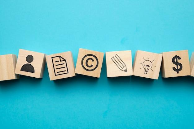 Conceito de direitos autorais com ícones em blocos de madeira.