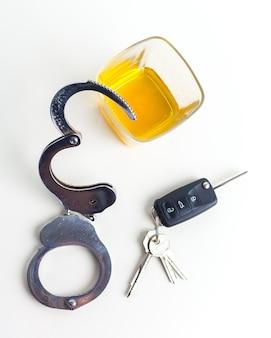 Conceito de dirigir embriagado - cerveja, chaves e algemas