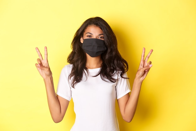 Conceito de distanciamento social covarde e retrato do estilo de vida de uma linda garota afro-americana com máscara facial preta, mostrando sinais de paz e sorrindo