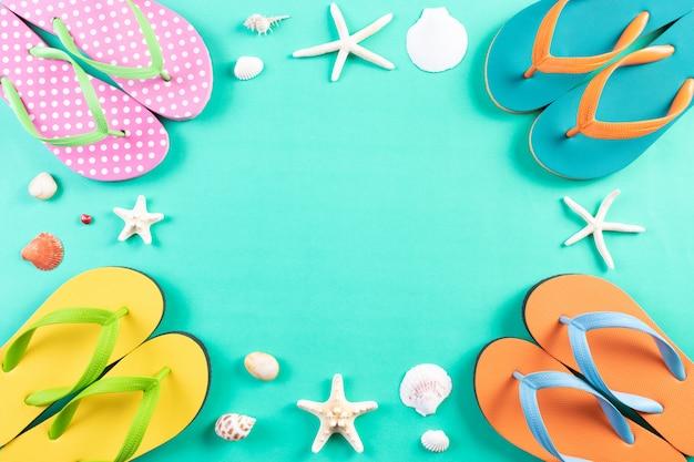 Conceito de distanciamento social de verão. quatro chinelos, estrelas do mar e conchas sobre fundo verde pastel.