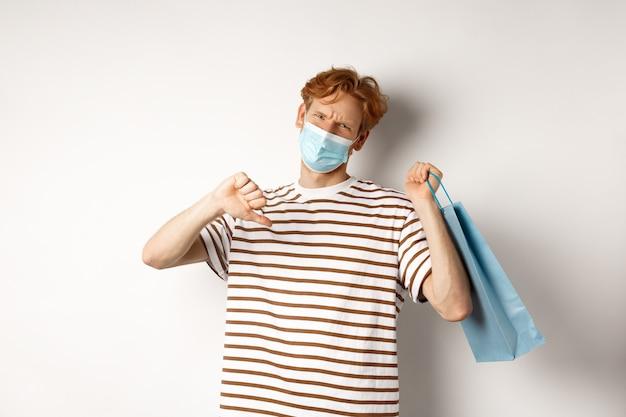 Conceito de distanciamento social e compras. jovem desapontado com cabelo ruivo, usando máscara, segurando sacola de compras e mostrando o polegar para baixo da loja de antipatia, reprovação.