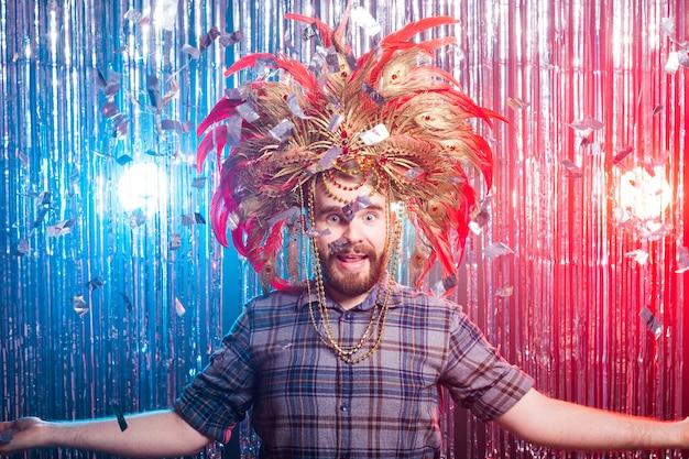 Conceito de diversão, feriado e dia da mentira - homem estranho com máscara e chapéu de carnaval